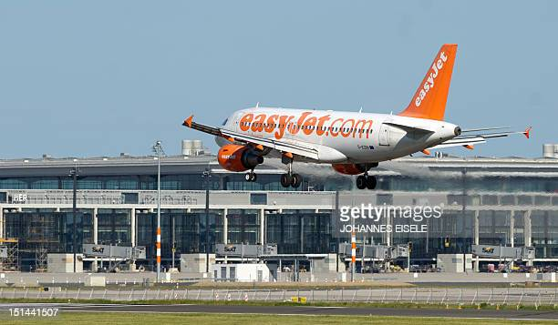 Picture taken on on May 25 2012 in Schoenefeld near Berlin shows an Easyjet aircraft landing at Schoenefeld Airport next to the terminal building of...