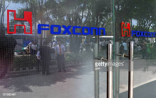 Picture taken on on May 26 2010 shows people reflected in a glass door bearing the logo of the Foxconn technology group at the company's plant in...
