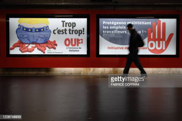 """Picture taken on September 1, 2020 in Lausanne shows backlit electoral posters that translates from French as """"Too much is too much!"""" and """"Protecting..."""