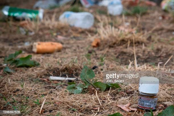A picture taken on September 13 2018 in Paris shows a bottle of methadone a legal heroin substitute amid garbage