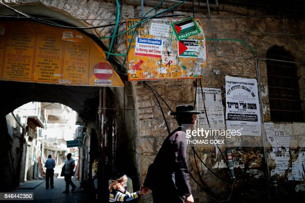 A picture taken on September 13 shows an UltraOrthodox Jew passing by some signs against the Israeli State and Zionist occupation in the...
