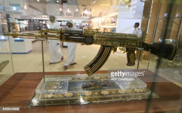 A picture taken on September 14 2017 shows an ornamented goldplated Kalashnikov AK47 assault rifle on display at the Abu Dhabi International Hunting...