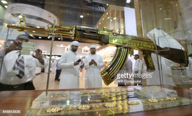 A picture taken on September 14 2017 shows Emirati men using their cellphones to take pictutres of an ornamented goldplated Kalashnikov AK47 assault...