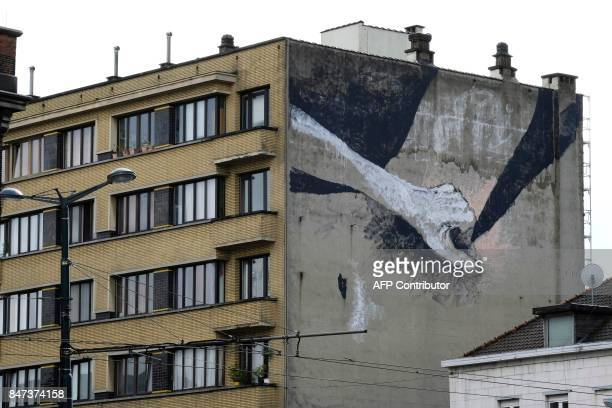 A picture taken on September 15 2017 shows a mural by an unidentified artist showing a woman's private parts being groped at the Rue de Witte de...
