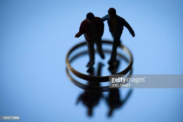 A picture taken on September 16 2012 in Paris shows an illustration made with two figurines in the centre of a wedding ring set up on a mirror to...