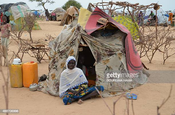 A picture taken on September 16 2015 shows a woman sitting in front of a tent in the Assaga refugee camp set up by the UN three months ago for...