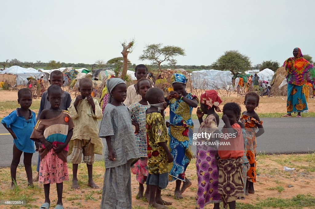 A picture taken on September 16, 2015 shows children standing in the Assaga refugee camp, set up by the UN three months ago for Nigerian refugees who fled to southeast Niger to escape the Islamist group Boko Haram. In the Assaga camp, many refugees live in abject poverty and sleep in makeshift shelters at the mercy of mosquitoes and bad weather, an AFP reporter saw.