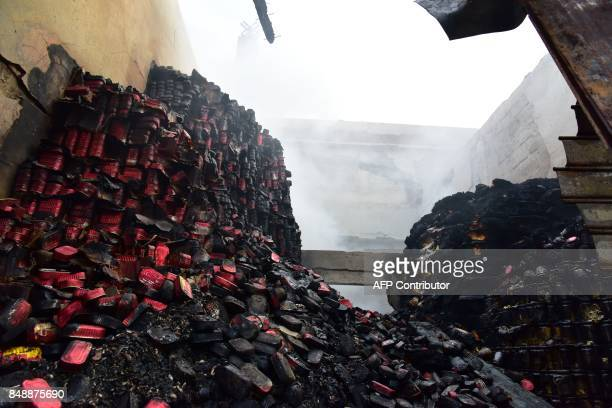 A picture taken on September 18 2017 in Abobo neighborhood of Abidjan shows burnt cans in the market after a fire devastated the building during the...
