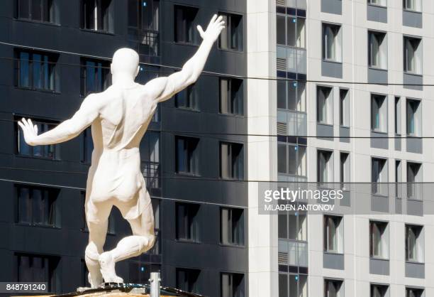 A picture taken on September 18 2017 shows a Soviet time sculpture placed in front of an apartment building at the Yekaterinburg Arena in...