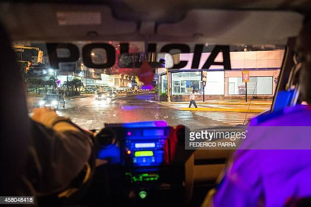 Picture taken on September 19 2014 showing Venezuelan policemen patrolling in the urban area of the municipality of Sucre in Caracas Venezuelan...
