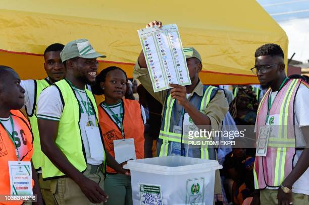 A picture taken on September 22 2018 shows an electoral officer raising a ballot to count results in a ward after the Osun State gubernatorial...