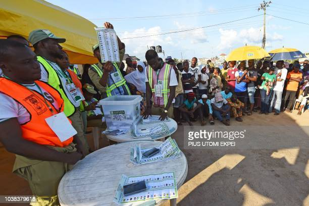 A picture taken on September 22 2018 shows people watching as an electoral officer raises a ballot to count results in a ward after the Osun State...