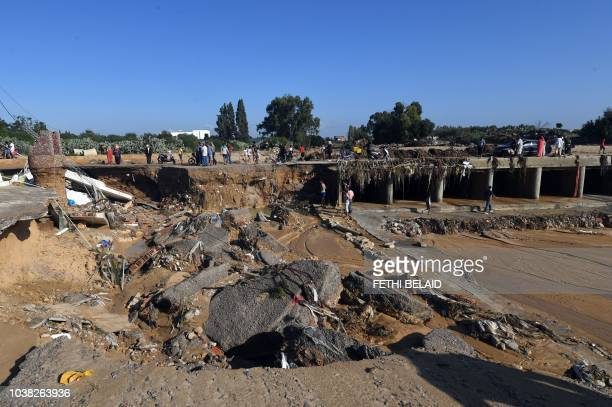 A picture taken on September 23 in the Tunisian coastal town of Nabeul shows people gathering at the site of a collapsed bridge following deadly...