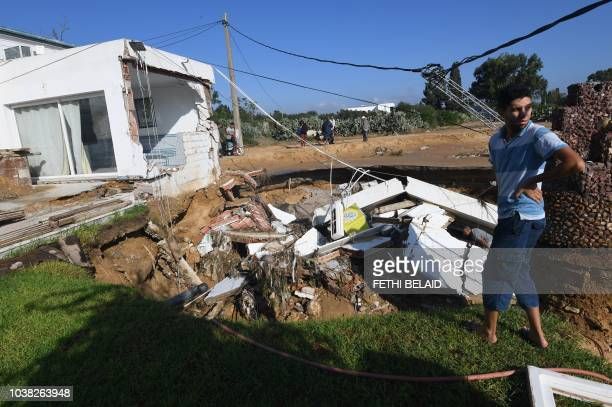 A picture taken on September 23 in the Tunisian coastal town of Nabeul shows people gathering at the site of a collapsed bridge and a damaged home...