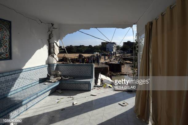 A picture taken on September 23 in the Tunisian coastal governante of Nabeul shows people gathering at the site of a collapsed bridge and a damaged...