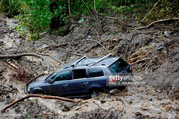 Picture taken on September 26 2018 in Bergen Norway shows a car stuck in the mud after heavy rainfall and flood hit the west coast of Norway causing...