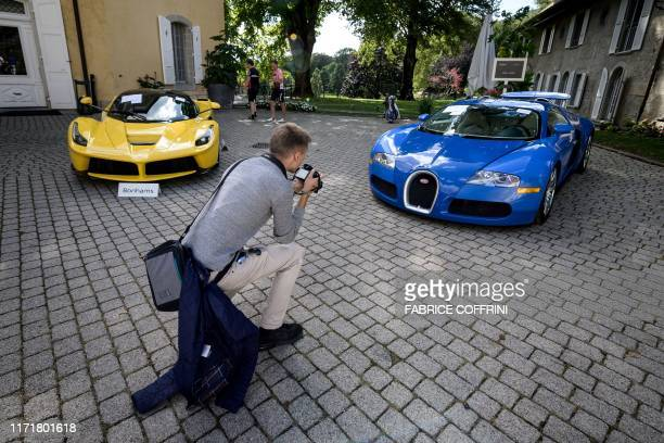 Picture taken on September 28, 2019 at the Bonmont Abbey in Cheserex, western Switzerland shows a 2015 Ferrari LaFerrari and a 2010 Bugatti Veyron EB...