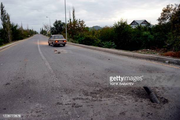 Picture taken on September 28, 2020 shows an unexploded artillery shell on a road on the outskirts of the Azerbaijani city of Tartar during clashes...