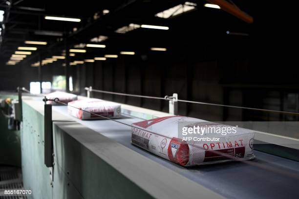 A picture taken on September 28 in MontalieuVercier shows bags of cement on the conveyor belt at the plant of the French cement manufacturer Vicat...