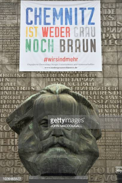"""Picture taken on September 3, 2018 in Chemnitz, eastern Germany, shows a poster reading """"Chemnitz is neither grey nor brown"""" fixed on the Karl Marx..."""