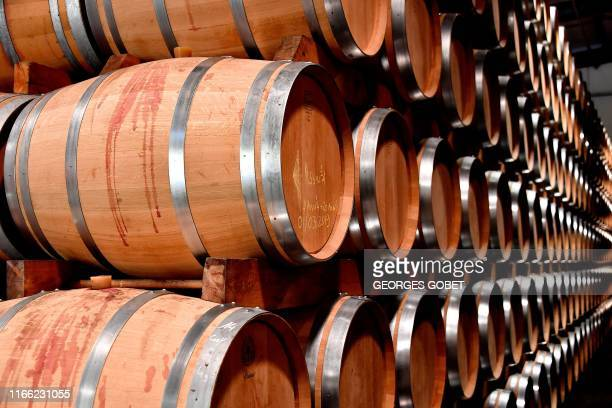 A picture taken on September 3 2019 shows wine barrels in Rauzan cooperative in the EntreDeuxMers region near Bordeaux southwestern France Harvest...