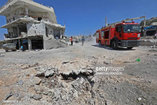 A picture taken on September 4 2018 shows a fire engine drives through a damaged road after a reported Russian air strikes in the rebelheld town of...