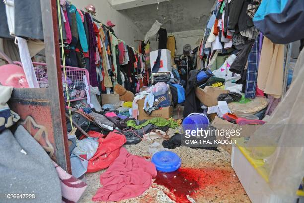 A picture taken on September 4 2018 shows damage and blood stain in a clothing shop after reported Russian air strikes in the rebelheld town of...