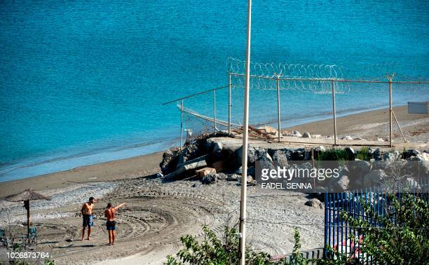 Picture taken on September 4, 2018 shows men gesturing towards a section of the border fence encircling Spain's North African enclave of Ceuta which...