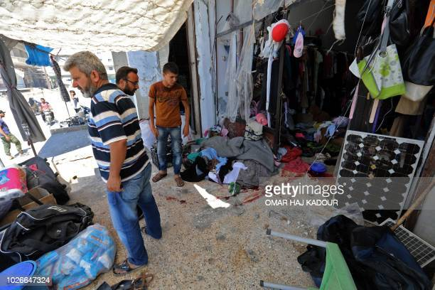 A picture taken on September 4 2018 shows Syrians inspect the damage in a clothing shop after reported Russian air strikes in the rebelheld town of...