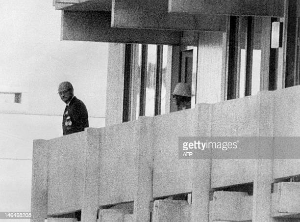 Picture taken on September 5, 1972 shows a Palestinian guerilla member appearing on the balcony of the Israeli house watching an official at the...