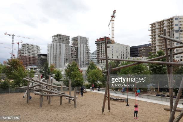 A picture taken on September 5 2017 shows cranes and under construction sites and children and families playing at the Martin Luther King garden in...