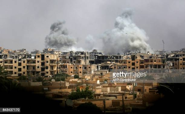 A picture taken on September 5 2017 shows smoke billowing out following a coalition air strike in the western alDaraiya neighbourhood of the...