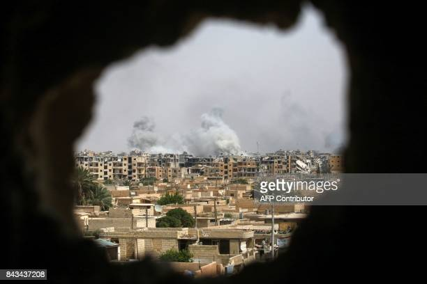 TOPSHOT A picture taken on September 5 2017 shows smoke billowing out following a coalition air strike in the western alDaraiya neighbourhood of the...