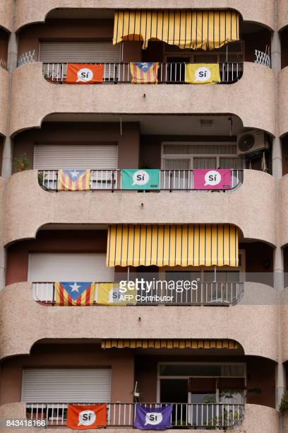 A picture taken on September 6 2017 shows a building with Esteladas and banners reading in Catalan 'YES' in Barcelona Spain's central government has...