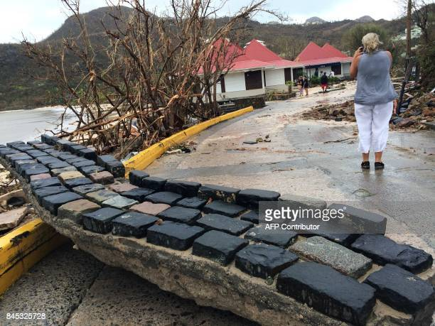 A picture taken on September 6 shows a woman taking a photo of damages as a detroyed wall lies on the street in Gustavia on the French Caribbean...
