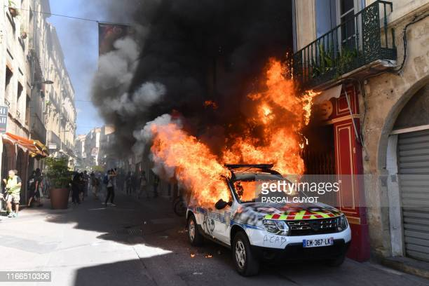 Picture taken on September 7, 2019 shows a burning French Municipal Police car on the sidelines of an anti-government demonstration called by the...