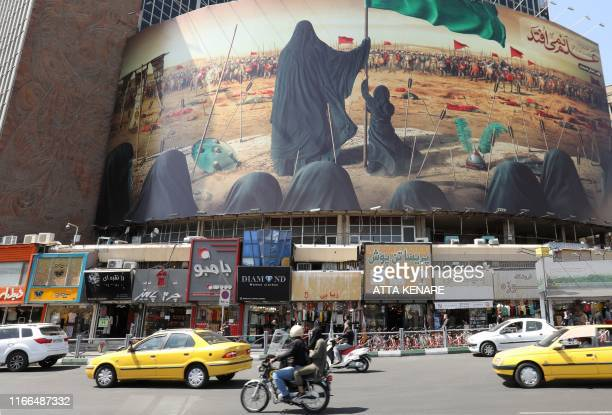 A picture taken on September 7 2019 shows traffic driving past a political mural at Vali Asr Square in the Iranian capital Tehran Iran said Saturday...