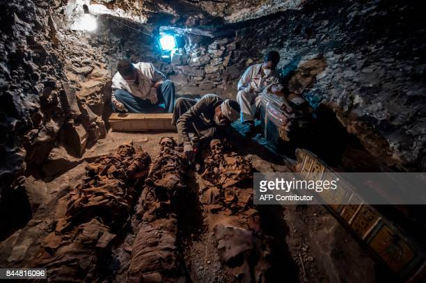 TOPSHOT A picture taken on September 9 2017 shows Egyptian labourers and archaeologists unearthing mummies at a newlyuncovered ancient tomb for a...