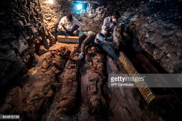 A picture taken on September 9 2017 shows Egyptian labourers and archaeologists unearthing mummies at a newlyuncovered ancient tomb for a goldsmith...