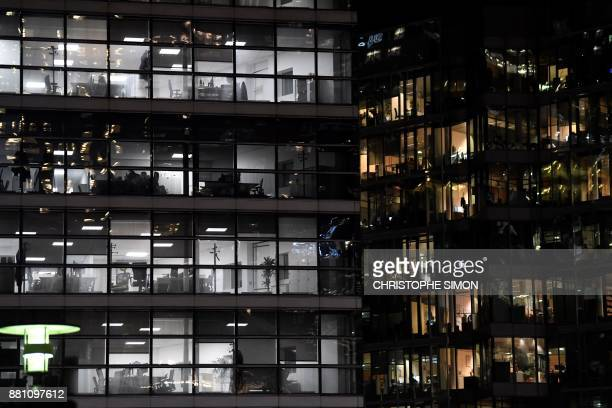 A picture taken on the esplanade of the business district of La Defense west of Paris on November 28 2017 shows lit up offices' windows / AFP PHOTO /...