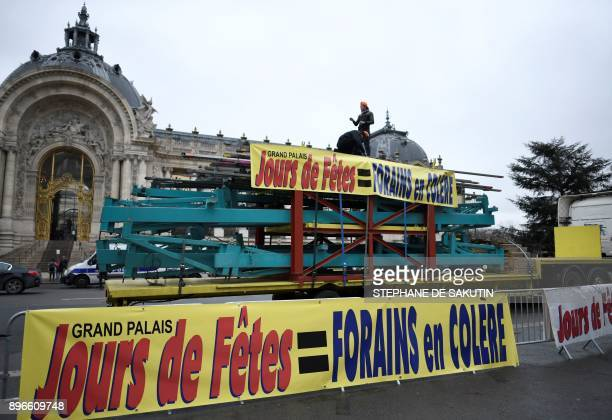 A picture taken outside the Grand Palais in Paris on December 21 2017 shows barriers and a truck bearing signs reading 'Jours de fetes funfair = fun...