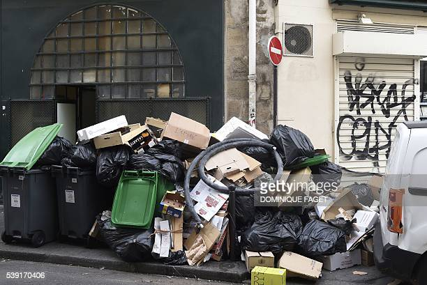 Picture taken shows rubbish bins surrounded by overflowing refuse sacks on the pavement in the centre of Paris on June 10 2016 The piles of...