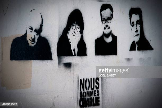 A picture taken shows stencils by French artist RobInk depicting slain cartoonists Wolinski Cabu Charb and Tignous and the words Je suis Charlie...