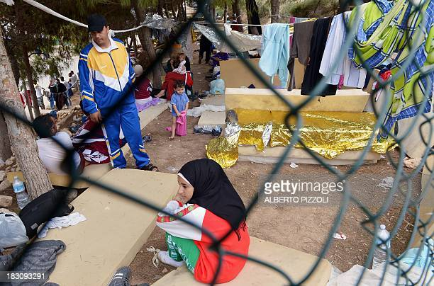 A picture taken through a fence shows migrants at the 'Temporary Permanence Centre' in Lampedusa on October 4 2013 Italy mourned today the 300...