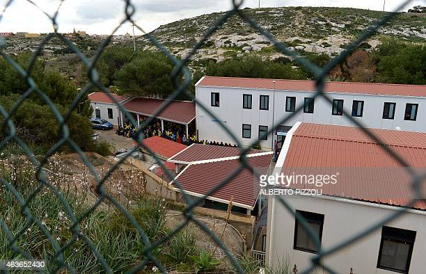 A picture taken through a fence shows migrants at the Temporary Permanence Centre a refugee camp on February 17 2015 in Lampedusa The Italian...