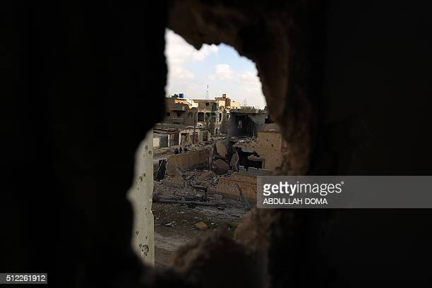 A picture taken through a hole in the wall shows damaged buildings after fighters loyal to Libya's internationally recognised government seized the...