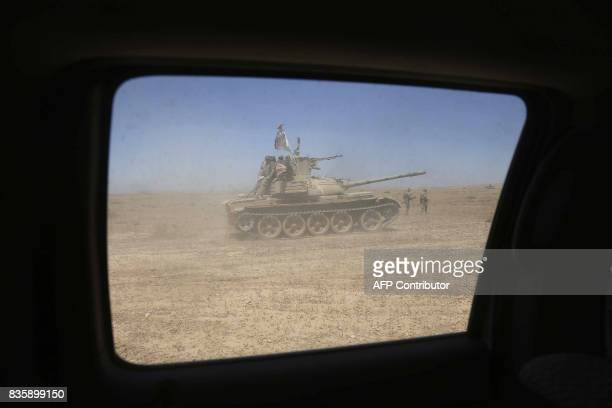 A picture taken through a windshield shows Iraqi government forces supported by fighters from the Abbas Brigade which fights under the umbrella of...
