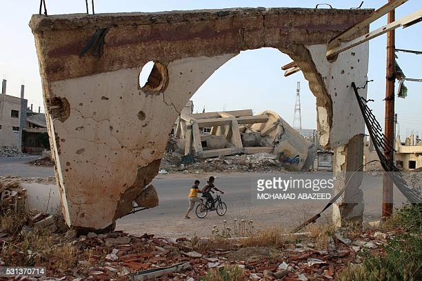 TOPSHOT A picture taken through an arch remaining from a detroyed building shows Syrian boys on a bicycle on May 14 2016 in the southern Syrian city...
