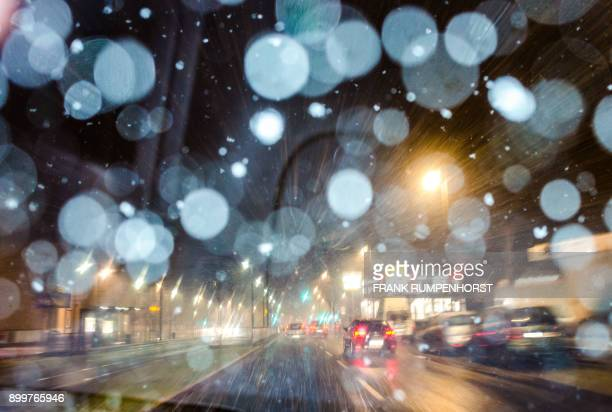 Picture taken through the windshield of a car shows snow falling on a street in Frankfurt am Main western Germany on December 29 2017 / AFP PHOTO /...