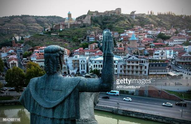 A picture taken with a drone on August 23 2017 shows a view of the Georgian capital of Tbilisi from behind the monument of King Vakhtang Gorgasali in...
